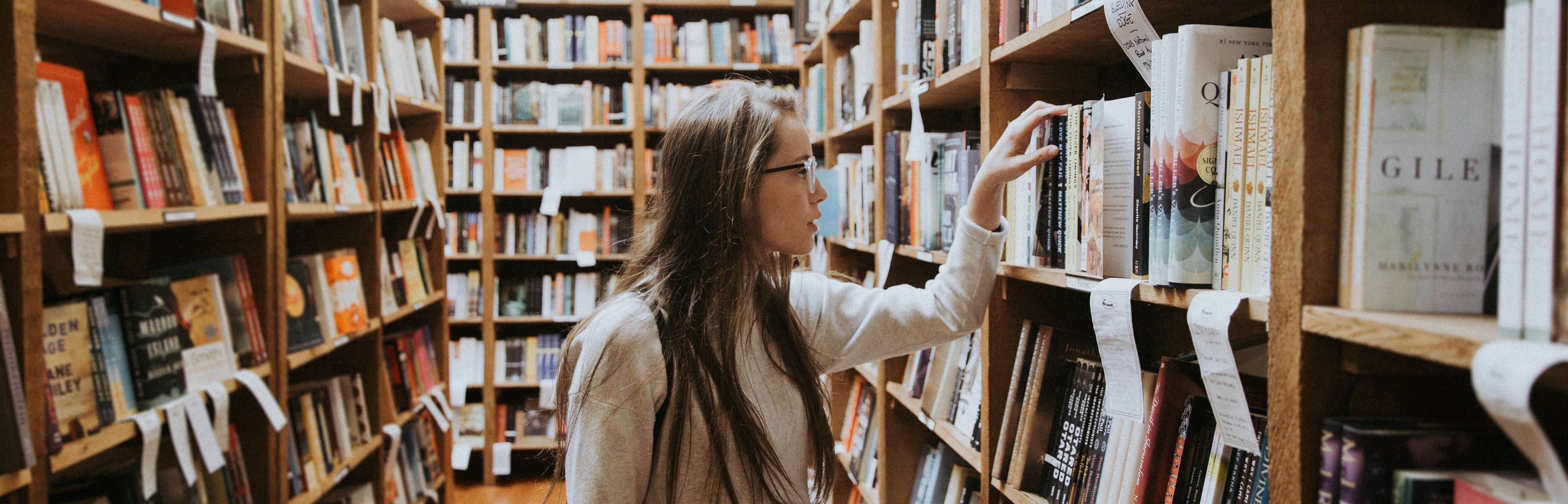 Photo by Becca Tapert on Unsplash. A woman holding library books amid library stacks.