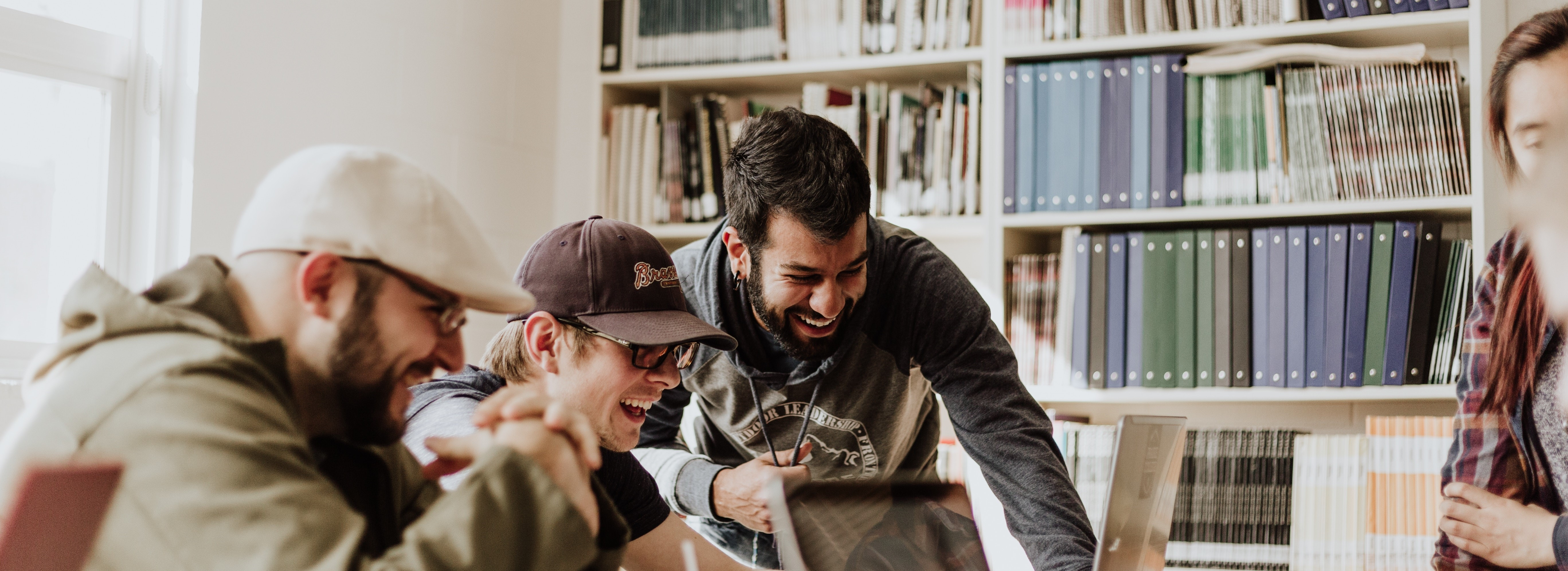 Photo by Priscilla Du Preez on Unsplash. three men laughing while looking in the laptop inside room.