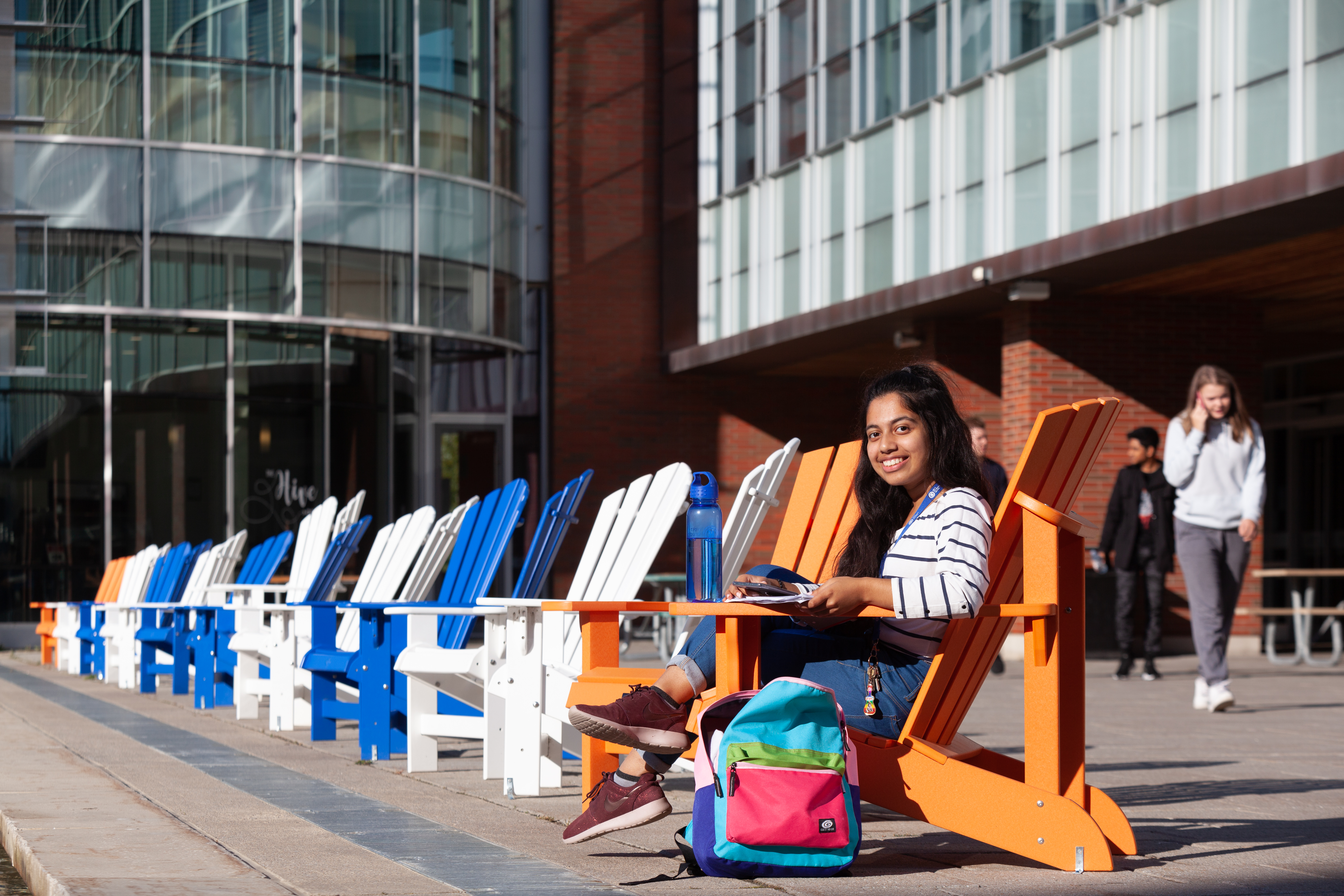student sitting in muskoka chairs outside the library