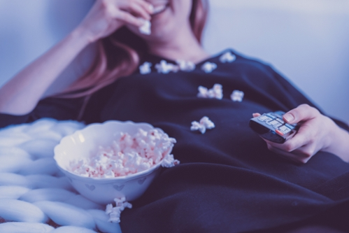 woman in black pyjamas laying on couch eating popcorn