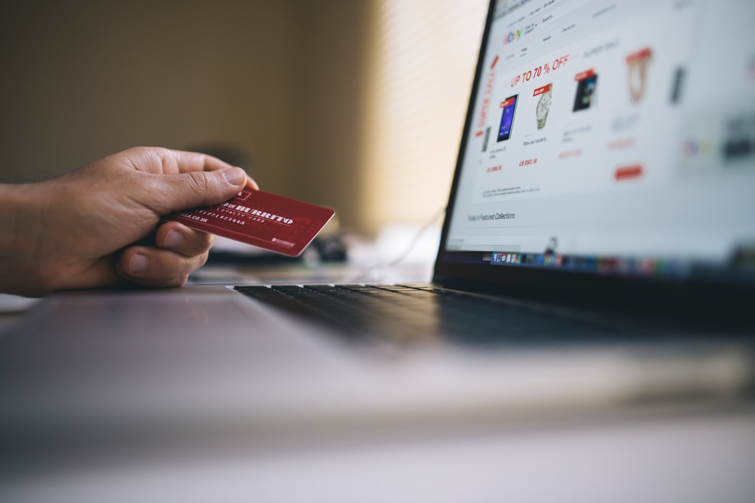 online shopping on a laptop with credit card in hand
