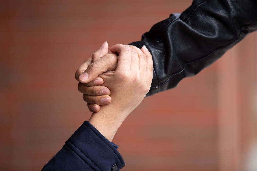 one hand holding another hand, to symbolize helping someone up