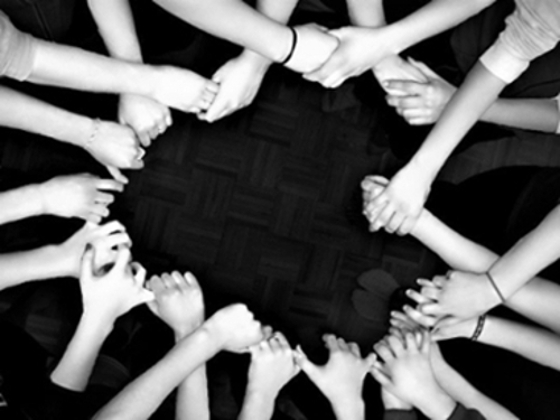 People standing in a circle holding hands