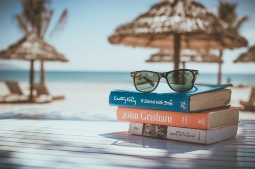 sunglasses on a stack of books on the beach