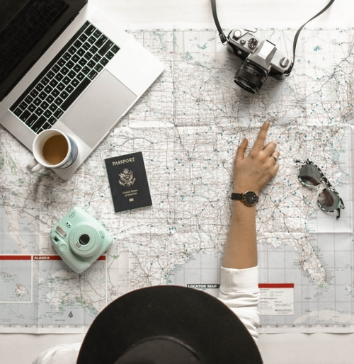 Girl wearing hat pointing at map with passport, camera, laptop, and coffee overtop.