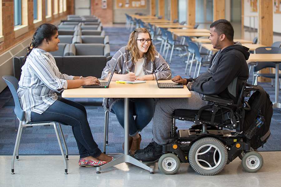 Student with in a wheelchair working with representatives from the university's Student Accessibility Services (SAS)