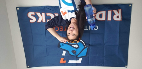 Student holding a Student Union water bottle wearing an Ambassador Shirt posing in front of a Ridgeback flag.