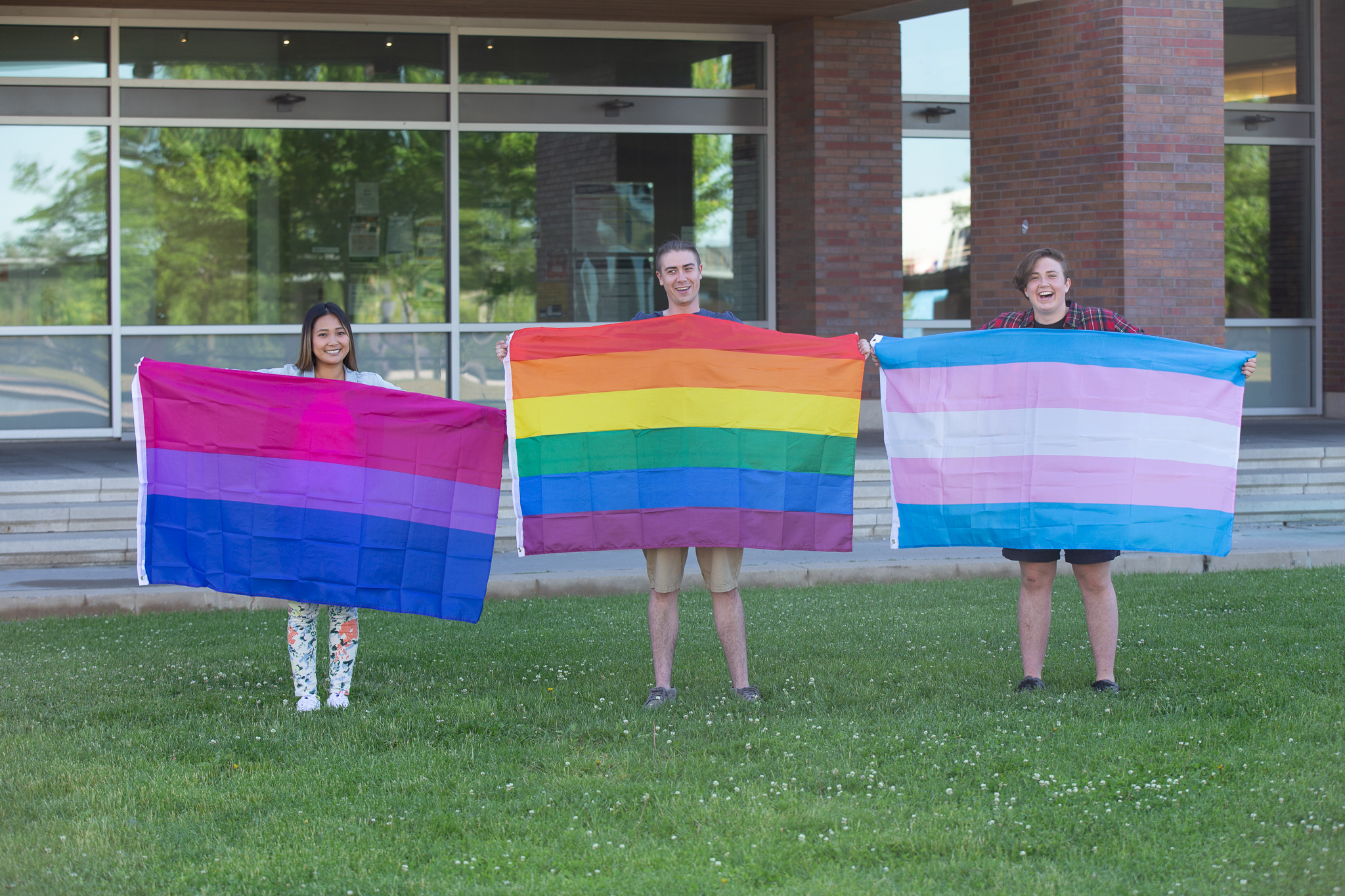 Four people holding pride flag