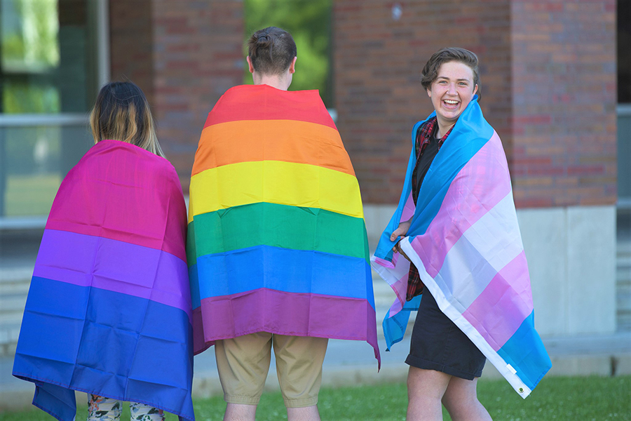 Students supporting equity and inclusion holding Pride flags.