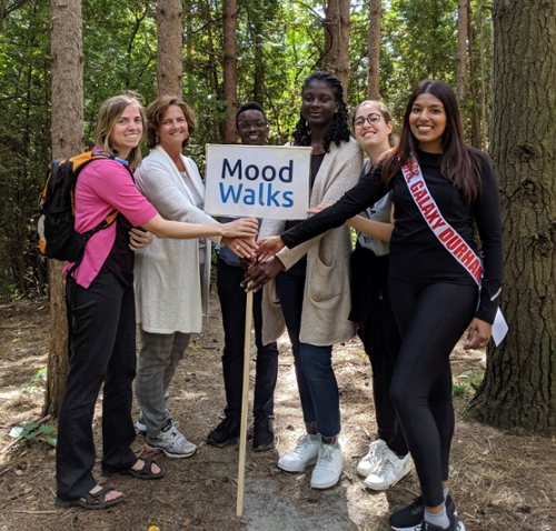 six women in the woods holding a mood walks sign