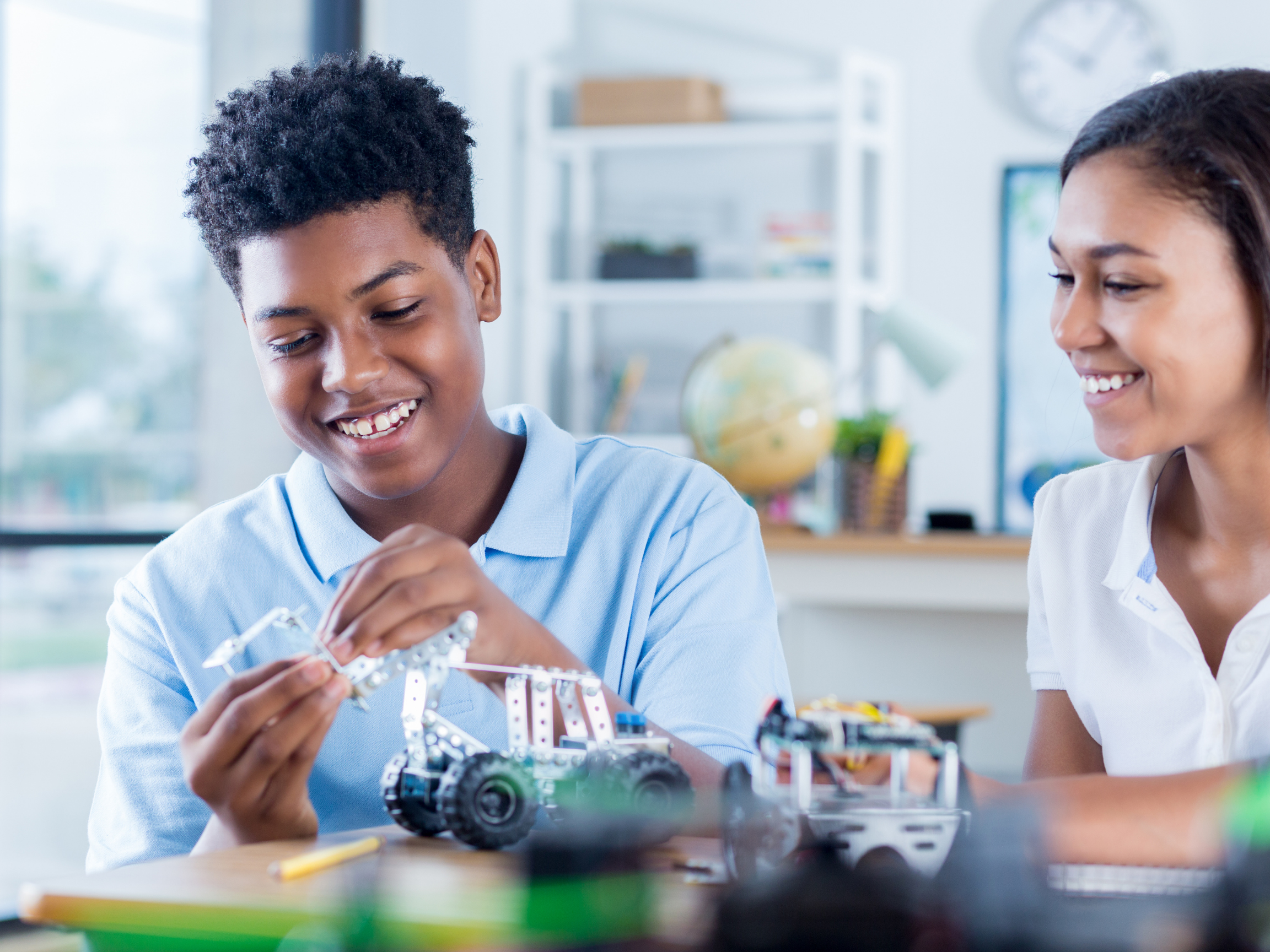 Photo of black youth working with robot