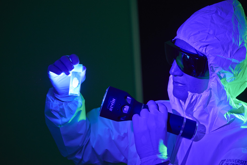 Forensic scientist shining an alternate light source on a glass slide to visualize a fingerprint.