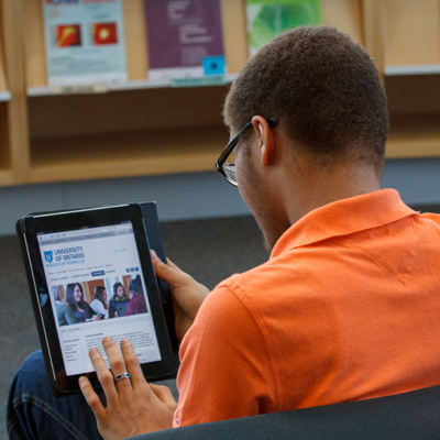 Student viewing the program information on a tablet in the library