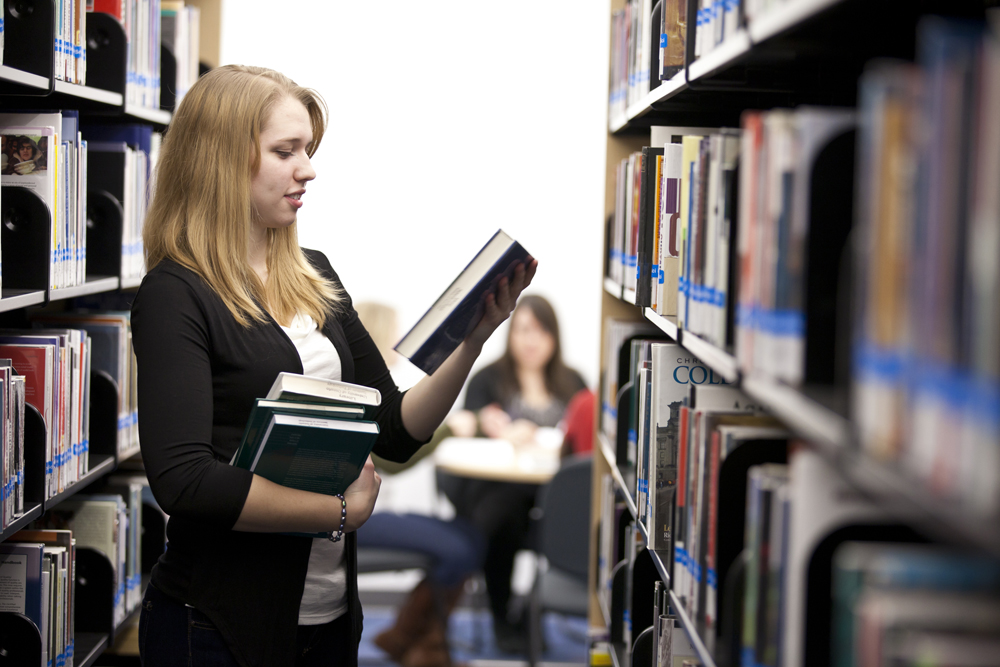 A student holding books on her right hand while reading a book on her left hand in the library aisle
