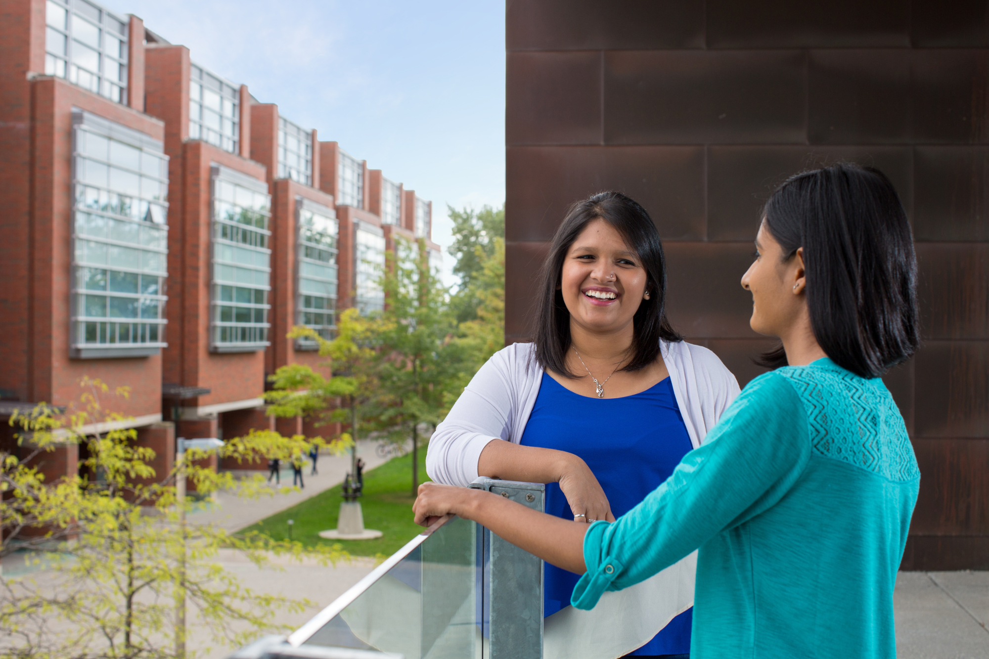 Two students speak with each other outside.